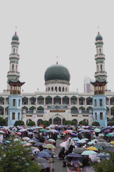 <b>XINING, CHINA:</b> Muslims wait to attend Friday prayers in the rain at the Dongguan Mosque in Xining, China. Dongguan Mosque is the biggest mosque in Qinghai Province. It was built in 1380, and now boasts a history of more than 600 years. The mosque is not only famous for its magnificent architecture but also as a religious education center and as the highest learning institution of Islam.
