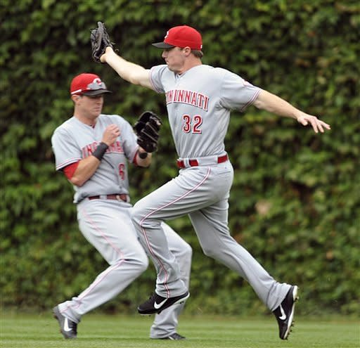 Cincinnati Reds' Drew Stubbs (6) almost collides with Jay Bruce (32) after Bruce caught a fly ball off the bat of Chicago Cubs' Anthony Rizzo during the fourth inning of a baseball game on Sunday, Aug. 12, 2012, in Chicago. (AP Photo/Jim Prisching)
