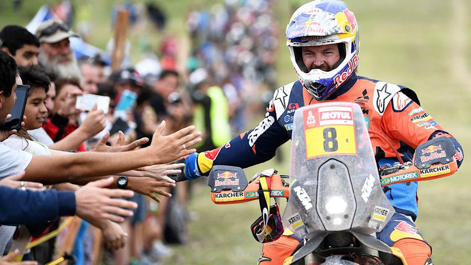 Toby Price is seen here high-fiving fans at the 2019 Dakar Rally.