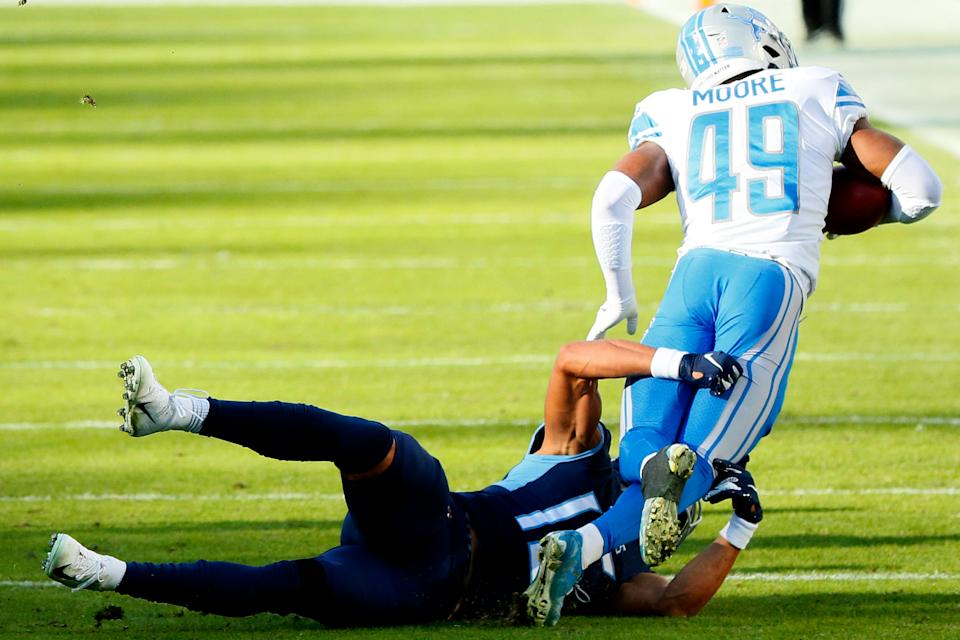 Safety C.J. Moore (49) of the Detroit Lions is tackled short of a first down by wide receiver Nick Westbrook (15) of the Tennessee Titans for a turnover on downs on a fake punt during the fourth quarter of the game at Nissan Stadium on Dec. 20, 2020 in Nashville, Tennessee.