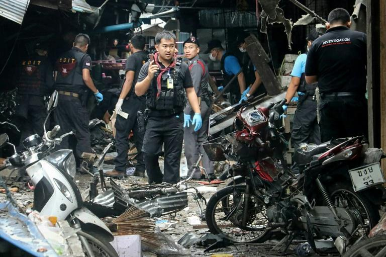 A Thai forensics unit scours the aftermath of a motorcycle bombing which killed three civilians and wounded others at a market in the restive southern Thai province of Yala on January 22, 2018