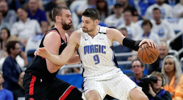 Orlando Magic's Nikola Vucevic (9) tries to get past Toronto Raptors' Marc Gasol. (AP Photo/John Raoux)