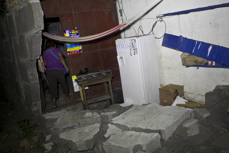 A woman walks inside a home that was damaged by an earthquake in Nagarote, Nicaragua, Thursday, April 10, 2014. A 6.1-magnitude earthquake damaged dozens of houses in western Nicaragua on Thursday, and authorities said some people were injured by falling ceilings, beams and walls. (AP Photo/Esteban Felix)