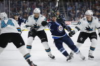 Winnipeg Jets' Nicholas Shore (21) tries to get through San Jose Sharks' Alexander True (70) and Patrick Marleau (12) during the second period of an NHL hockey game Friday, Feb. 14, 2020, in Winnipeg, Manitoba. (John Woods/The Canadian Press via AP)