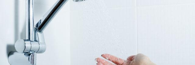 hand reaches towards shower head and water