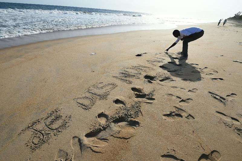 """A man scratches in the sand the words, """"I say no to terrorism,"""" close to the Hotel Etoile du Sud, in Grand-Bassam, Ivory Coast on March 16, 2016 (AFP Photo/Sia Kambou)"""