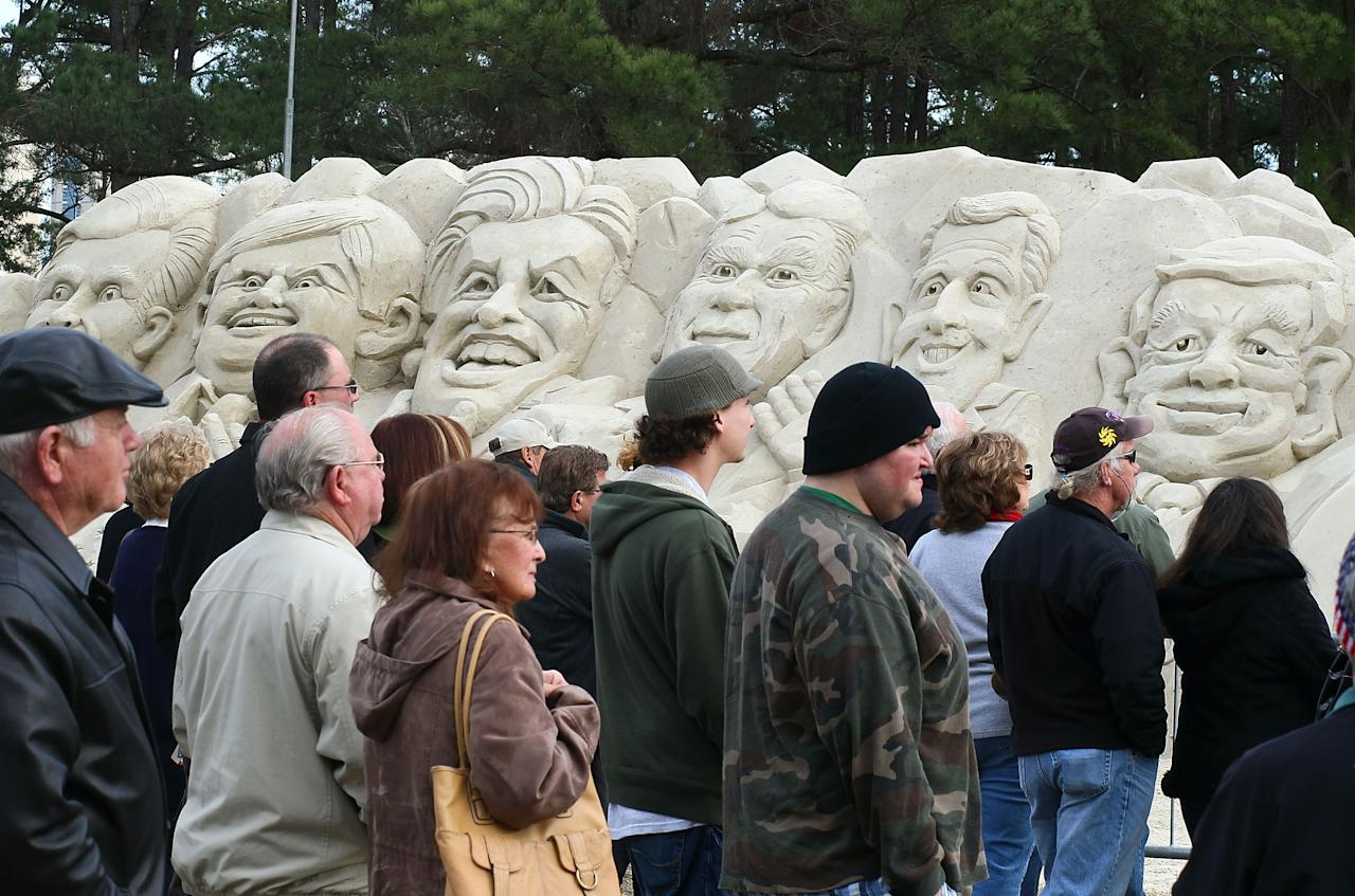 MYRTLE BEACH, SC - JANUARY 16: People stand in front of a sand sculpture depicting Republican presidential candiates (L-R) Mitt Romney, Newt Gingrich, former candidate Jon Huntsman, Rick Perry, Rick Santorum and Ron Paul, in front of the Myrtle Beach Convention Center, on January 16, 2012 in Myrtle Beach, South Carolina. Later tonight all the remaining Republican candidates will participate in a 90 minute debate. (Photo by Mark Wilson/Getty Images)