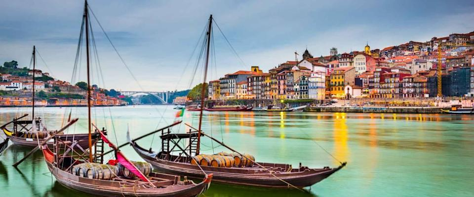Porto, Portugal old town cityscape on the Douro River with traditional Rabelo boats.