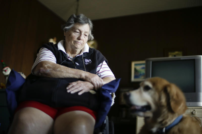 In this Dec. 10, 2013 photo, Sherry Scott sits in a wheel chair, alongside her 10-year-old golden retriever Tootie, at her home in San Diego. Scott, who receives dog food for Tootie through the Animeals program, said she would give her lasagne and pork riblets from Meals on Wheels to Tootie if MOW didn't bring dog food for the dog. The pet food program is sponsored by the Helen Woodward Animal Center. (AP Photo/Gregory Bull)
