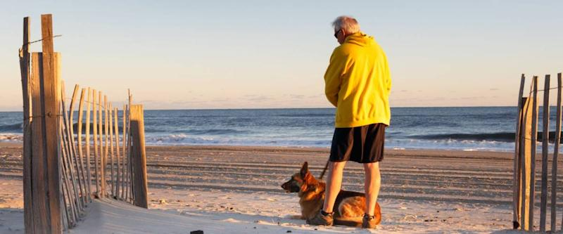 Senior man with dog enjoying a morning on a sandy beach in the Outer Banks of North Carolina.