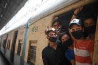 Passengers wearing facemasks travel in a train during a one-day Janata (civil) curfew imposed as a preventive measure against the COVID-19 coronavirus, at a railway station in Kolkata on March 22, 2020. - Nearly one billion people around the world were confined to their homes, as the coronavirus death toll crossed 13,000 and factories were shut in worst-hit Italy after another single-day fatalities record. (Photo by Dibyangshu SARKAR / AFP) (Photo by DIBYANGSHU SARKAR/AFP via Getty Images)
