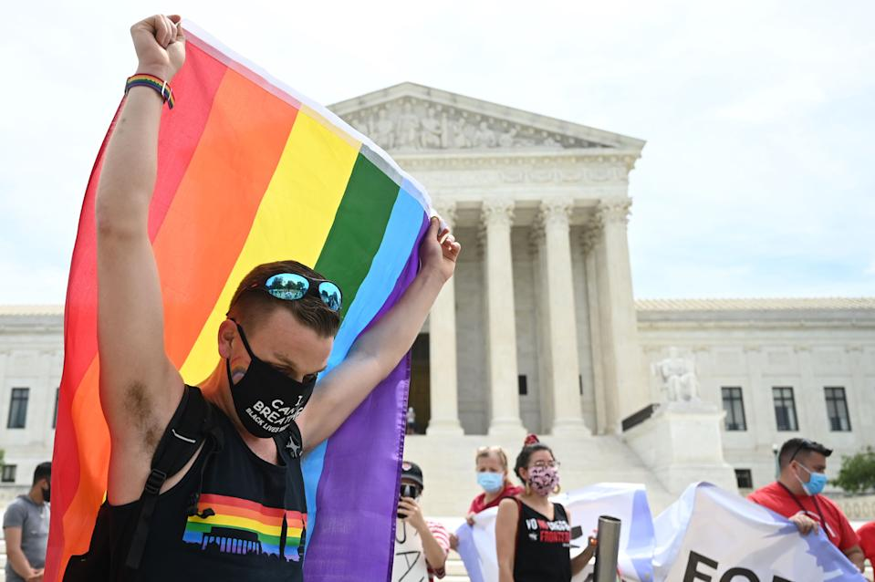 A reveler waves a rainbow flag in front of the U.S. Supreme Court that released a decision that says federal law protects LGBTQ workers from discrimination on June 15, 2020 in Washington,DC. - The US top court has ruled it illegal to fire workers based on sexual orientation. (Photo by JIM WATSON / AFP) (Photo by JIM WATSON/AFP via Getty Images)