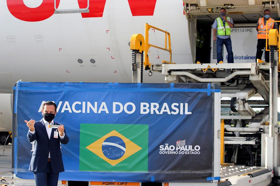 "Brazil's Sao Paulo state Governor, Joao Doria, holds a box of the China's Sinovac COVID-19 vaccine as refrigerated containers with vaccines arrive at Sao Paulo International Airport in Guarulhos, Brazil December 30, 2020. The banner reads ""Brazil's vaccine"". REUTERS/Amanda Perobelli"