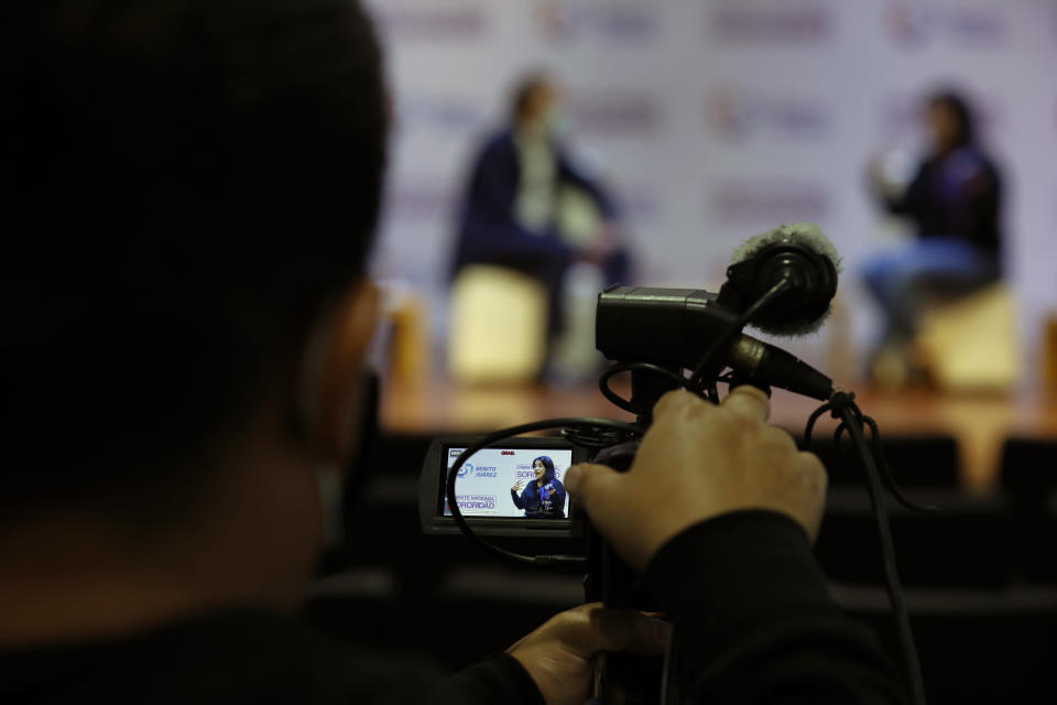 """A cameraman films for live broadcast as Olimpia Coral Melo, who became an activist against online sexual harassment and assault after a video of her having sex was published online in 2013, speaks with Benito Juarez borough Mayor Santiago Taboada, in Mexico City, Monday, Nov. 23, 2020. Melo's story and subsequent activism have led to the creation of numerous state laws against cyber violence, and Mexico's government is on the verge of passing a federal version of """"Olimpia's Law."""" (AP Photo/Rebecca Blackwell)"""