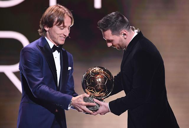 Luka Modric gives his trophy to Lionel Messi (Credit: Getty Images)