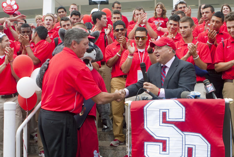 In this photo provided by Stony Brook University Communications, university president Samuel L. Stanley, right, welcomes Stony Brook Seawolves baseball head coach Matt Senk home from Baton Rouge, La., Monday, June 11, 2012, at Stony Brook, N.Y. The team upset college baseball's powerhouse, the LSU Tigers, in the NCAA college baseball super regional competition Sunday to earn a berth in the College World Series. (AP Photo/Stony Brook University Communications, John Griffin)