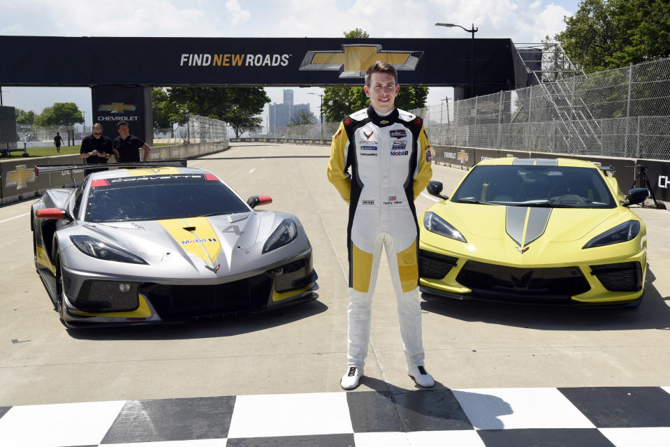 Tommy Milner stands in front of a Corvette C8.R race car, left, and a 2022 Corvette Stingray IMSA GTLM Championship Edition road car following a news conference at Raceway at Belle Isle, Wednesday, June 9, 2021, in Detroit. With Le Mans rescheduled to August, the conflict that had prevented Corvette from competing at Belle Isle had been eliminated and the two-car program will race Saturday in GM's backyard for the first time since 2008. (AP Photo/Jose Juarez)