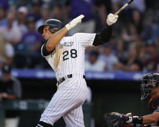 Colorado Rockies' Nolan Arenado follows the flight of his two-run home run off Miami Marlins starting pitcher Wei-Yin Chen in the fourth inning of a baseball game Friday, June 22, 2018, in Denver. (AP Photo/David Zalubowski)
