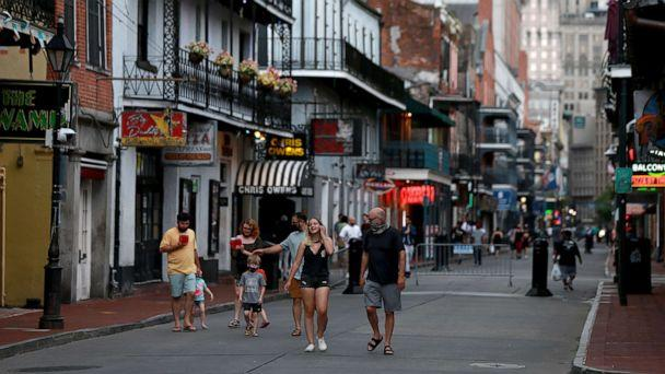 PHOTO: Pedestrians are seen walking along Bourbon Street in the French Quarter on July 14, 2020 in New Orleans. (Sean Gardner/Getty Images)