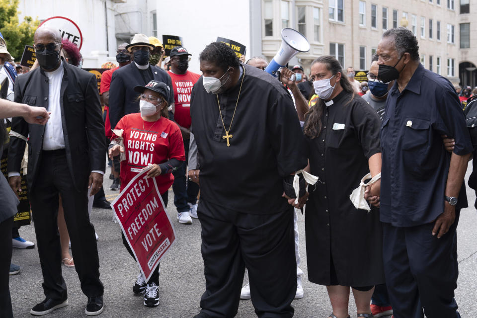 Rev. William Barber accompanied by Rev. Liz Theoharis and Rev. Jesse Jackson right, protest, during the Voting Rights rally on Capitol Hill, in Washington, Monday, Aug. 2, 2021. (AP Photo/Jose Luis Magana)