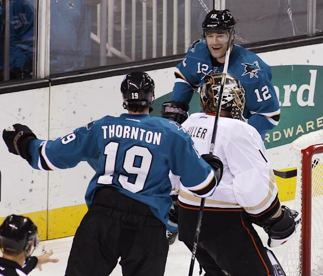 San Jose Sharks' Patrick Marleau, back, reacts after scoring a goal against the Anaheim Ducks, during the second period of an NHL hockey game, Saturday, Nov. 30, 2013, in San Jose, Calif. In front are Sharks' Joe Thornton (19) and Ducks goalie Jonas Hiller. (AP Photo/George Nikitin)