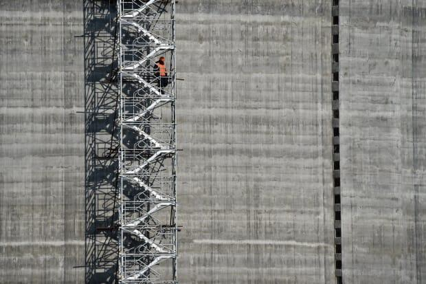 A worker standing on the stairs of a natural gas reservoir at the port of Sabetta in the Arctic circle. The lack of reporting requirements on fly-in workers can leave them exposed to discrimination and exploitation, said Alexandra Middleton, an assistant professor at the University of Oulu in Finland.