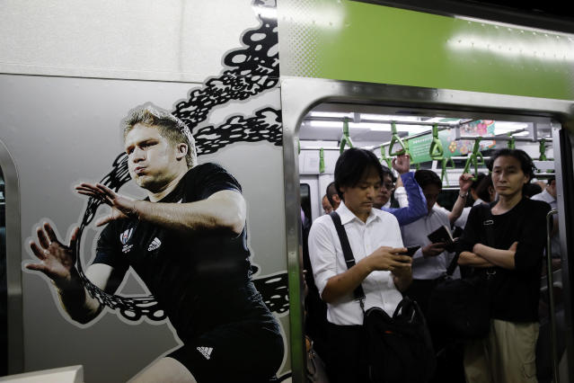 Commuters stand next an advertising picture for the Japan 2019 Rugby World Cup in the Tokyo subway, Japan, Thursday, Sept. 19, 2019. The Rugby World Cup starts Friday, Sept. 20, with Japan playing Russia, and ends with the final on Nov. 2. (AP Photo/Christophe Ena)