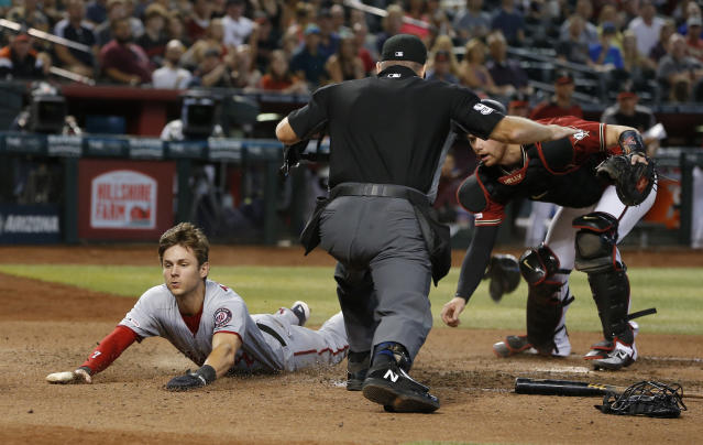 Washington Nationals' Trea Turner, left, scores a run on a ball hit by Anthony Rendon in the seventh inning during a baseball game against the Arizona Diamondbacks, Sunday, Aug. 4, 2019, in Phoenix. (AP Photo/Rick Scuteri)