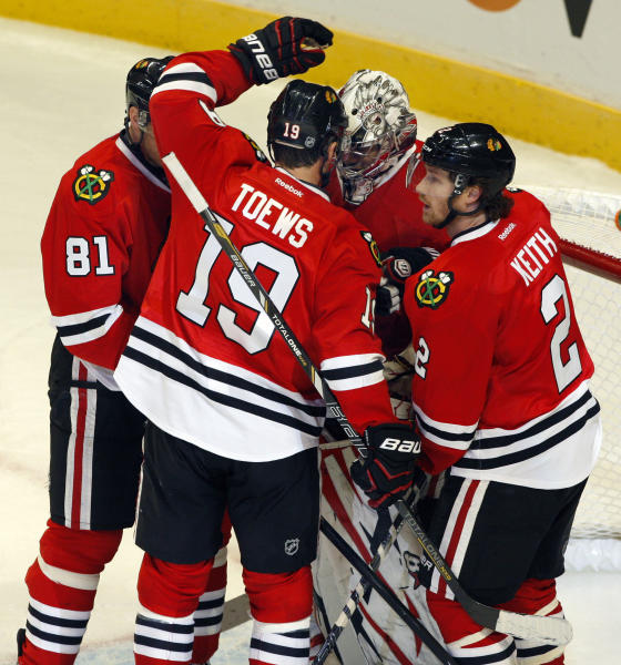 Chicago Blackhawks' Marian Hossa (81), Jonathan Toews (19) and Duncan Keith (2) congratulate goalie Ray Emery after they defeated the Los Angles Kings 3-2 on Sunday, Feb. 17, 2013, in Chicago. (AP Photo/John Smierciak)