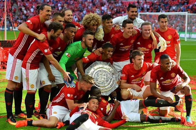 Manchester United players pose with the Community Shield on August 7, 2016 (AFP Photo/Glyn Kirk)
