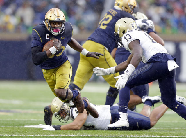 Notre Dame running back Josh Adams (33) goes around Navy safety Juan Hailey (13) during the first half of an NCAA college football game in South Bend, Ind., Saturday, Nov. 18, 2017. (AP Photo/Michael Conroy)