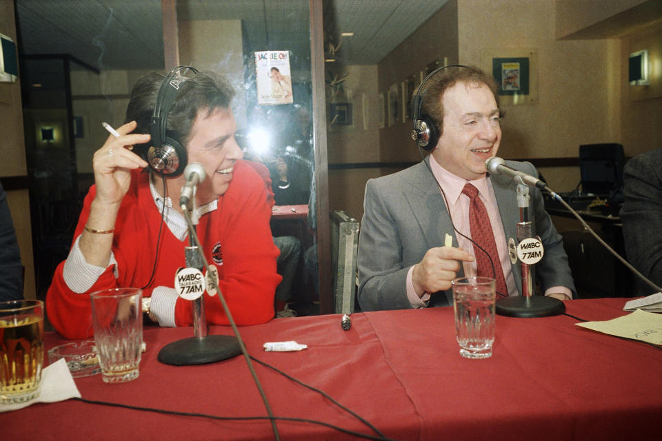 FILE - In this Nov. 24, 1988, file photo, comedian Jackie Mason, right, hosts TV personality Morton Downey Jr. during a live radio broadcast from Golden's Restaurant on West 51st Street in New York. Mason was also hosting the traditional Thanksgiving Day dinner for theater people working on the holiday. Mason, a rabbi-turned-jokester whose feisty brand of standup comedy got laughs from nightclubs in the Catskills to West Coast talk shows and Broadway stages, has died. He was 93. Mason died Saturday, July 24, 2021, in Manhattan, the celebrity lawyer Raoul Felder told The Associated Press. (AP Photo/Frankie Ziths, File)