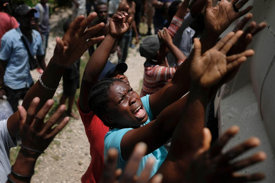 Earthquake victims reach for water being handed out during a food distribution in the Picot neighborhood in Les Cayes, Haiti on Aug. 22, 2021.