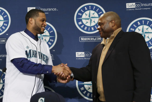 Robinson Cano, left, shakes hands with Seattle Mariners manager Lloyd McClendon, right, after being introduced as the newest member of the Mariners baseball team on Thursday, Dec. 12, 2013, in Seattle. (AP Photo/Ted S. Warren)