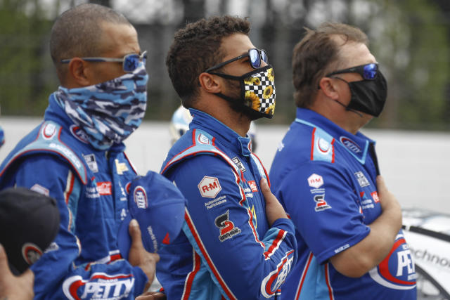 Bubba Wallace, center, stands with his crew during the playing of the national anthem before a scheduled NASCAR Cup Series auto race at Pocono Raceway, Saturday, June 27, 2020, in Long Pond, Pa. (AP Photo/Matt Slocum)