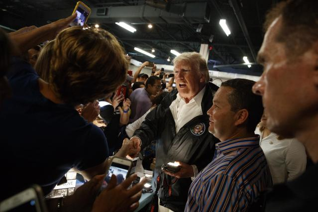 <p>President Donald Trump shakes hands and hands out flashlights and other supplies at Calvary Chapel, Tuesday, Oct. 3, 2017, in Guaynabo, Puerto Rico. (Photo: Evan Vucci/AP) </p>