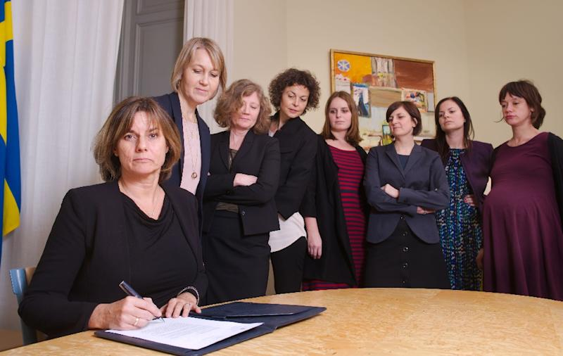 Isabella Lovin (left) signs a bill that would bind all future Swedish governments to net zero emissions by 2045