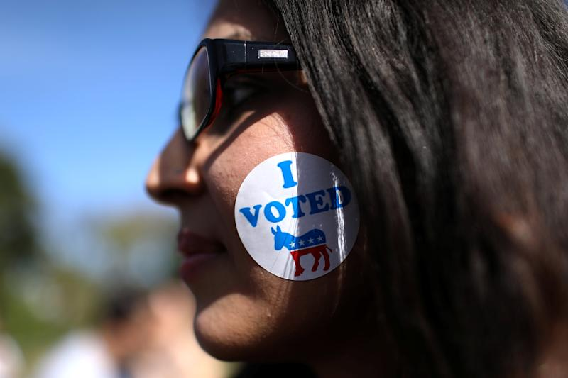 A woman wears a sticker on her face as she listens to U.S. Rep. Beto O'Rourke (D-TX) during the last day of early voting in Texas in Plano