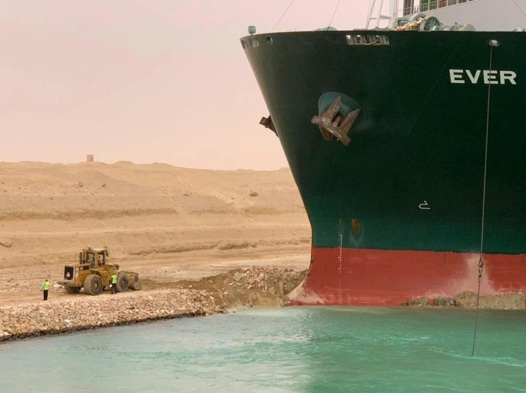 A handout picture released by the Suez Canal Authority on Wednesday shows a part of the MV Ever Given lodged sideways and blocking traffic on Egypt's Suez Canal