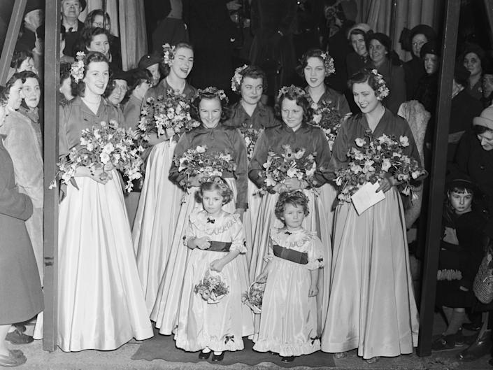 Camilla Duchess of Cornwall as a young bridal attendant. A group of women wear long gowns and hold bouquets.