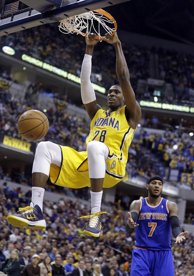 Indiana Pacers center Ian Mahinmi (28) gets a dunk in front of New York Knicks forward Carmelo Anthony during the second half of an NBA basketball game in Indianapolis, Thursday, Jan. 16, 2014. The Pacers defeated the Knicks 117-89. (AP Photo/Michael Conroy)