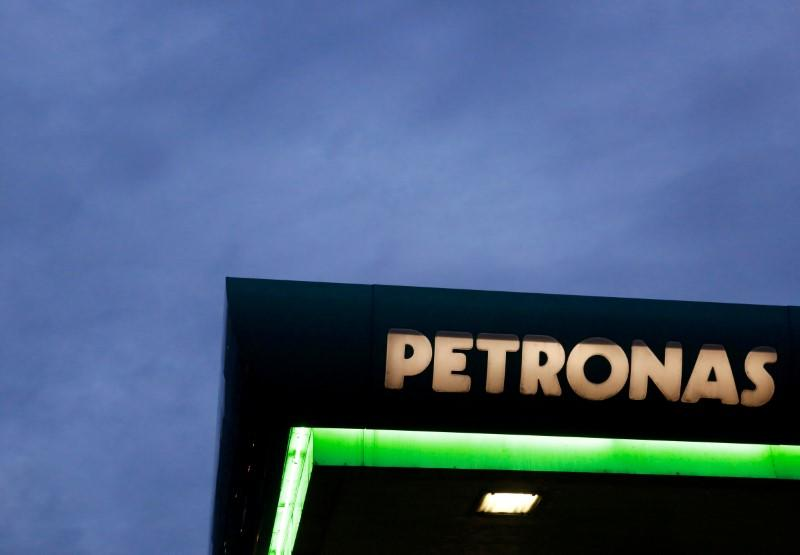 FILE PHOTO - A logo of a Petronas fuel station is seen against a darkening sky in Kuala Lumpur