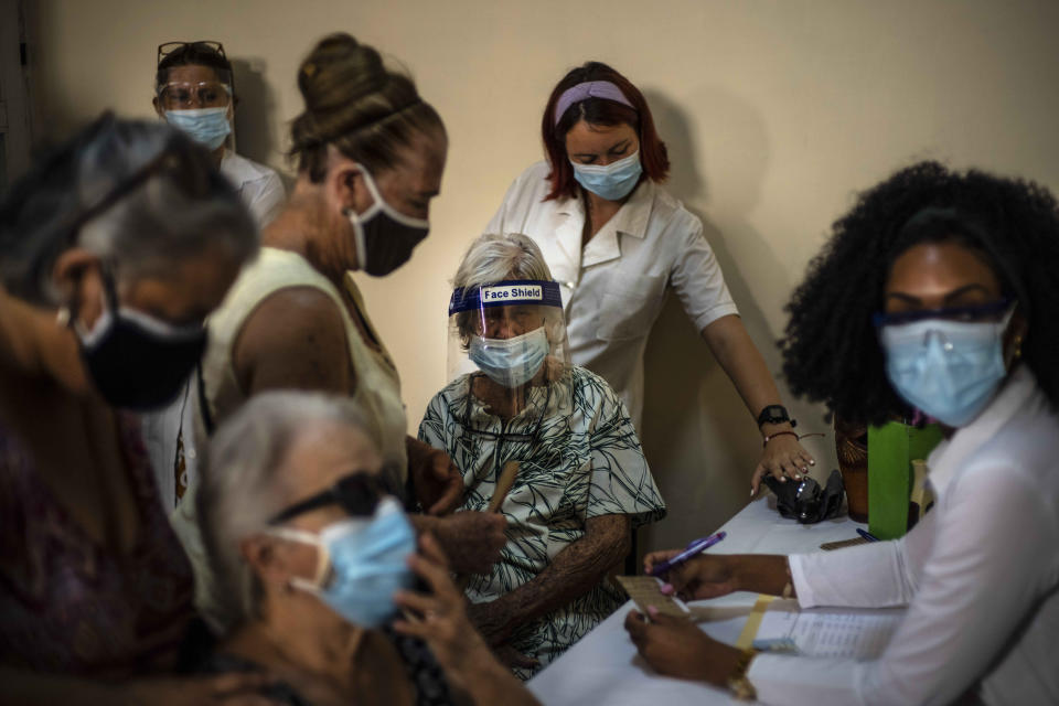 FILE - In this June 23, 2021 file photo, people sign up for a dose of the Cuban Abdala COVID-19 vaccine in Havana, Cuba. Cuba has been trying to rapidly roll out the two vaccines that it has approved for massive use, Abdala and Soberana, both of which require three jabs. (AP Photo/Ramon Espinosa, File)