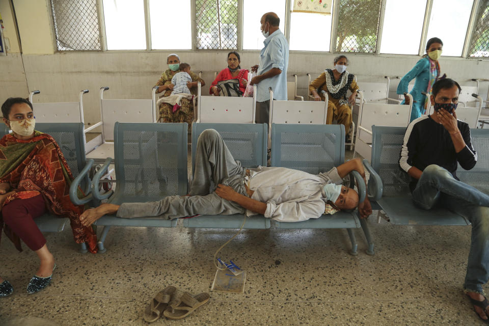 People wearing face masks as a precaution against the coronavirus wait for doctor consultation at a government hospital in Jammu, India, Monday, June 21, 2021. (AP Photo/Channi Anand)