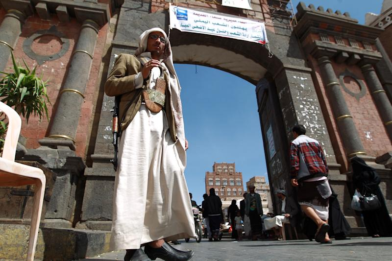 A Yemeni gunman loyal to the Shiite Muslim Huthi movement stands guard at the main gate of the old city of Sanaa on October 10, 2014 (AFP Photo/Mohammed Huwais)
