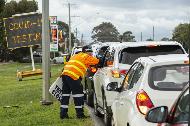 A man holding a sign saying 'testing closed' directs cars outside a COVID-19 testing site at Craigieburn Health in Melbourne, Tuesday, June 23, 2020.