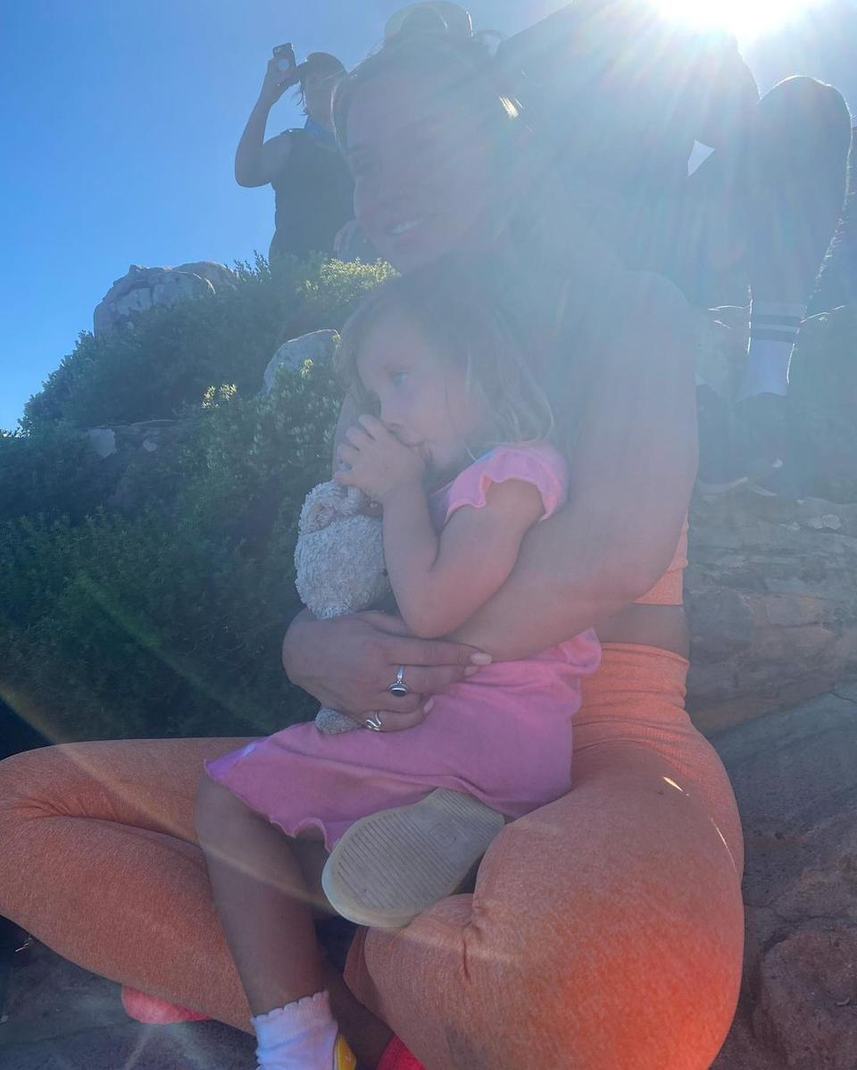 Ferne McCann in orange workout gear on a mountain in South Africa with her daughter Sunday