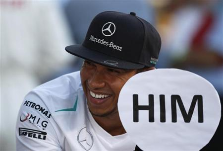 Mercedes Formula One driver Lewis Hamilton of Britain smiles after an autograph session for fans at the Suzuka circuit October 10, 2013, ahead of Sunday's Japanese F1 Grand Prix. REUTERS/Issei Kato