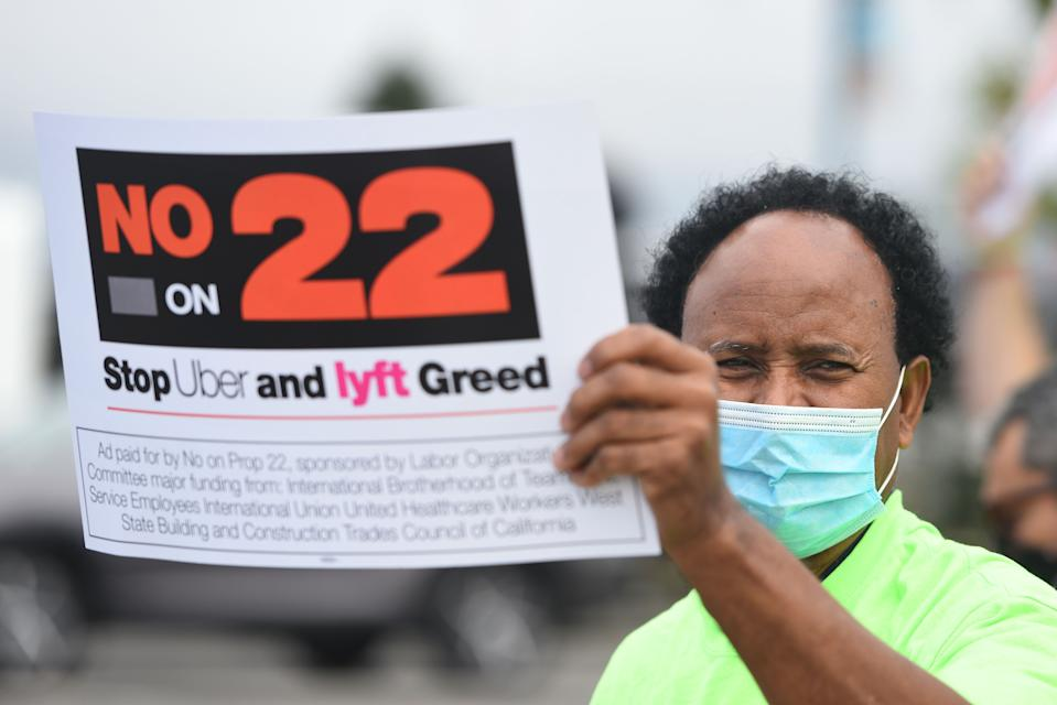 """A rideshare driver holds up a sign supporting a no vote on Prop 22 in Oakland, California on October 9, 2020. - Ahead of a referendum that could upend the whole gig economy, Uber driver Karim Benkanoun says his relationship with the rideshare giant must stop being a one-way street. """"If youre a driver with Uber or Lyft, you're nothing,"""" said Benkanoun as he speaks of how he will vote in California's Proposition 22 referendum. (Photo by JOSH EDELSON / AFP) (Photo by JOSH EDELSON/AFP via Getty Images)"""