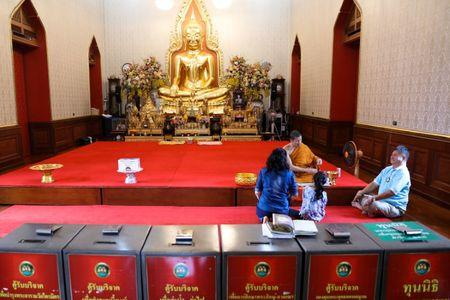 Tourists pray as donation boxes are seen at a temple in Bangkok, Thailand, Octoboer 18, 2017. Picture taken October 18, 2017. REUTERS/Athit Perawongmetha